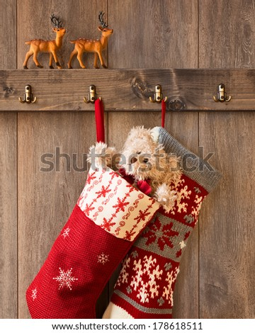 Pair of Christmas stockings hanging from hooks with reindeer figures sitting on the ledge - stock photo