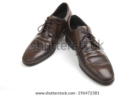 Pair of classic brown leather Polish mens shoes with laces and low heels for formal wear and dressing for the office, high angle on white - stock photo