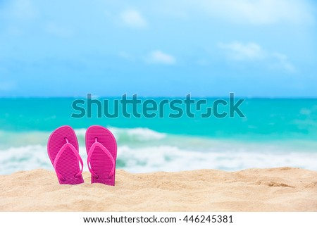 Pair of colorful slippers on the beach.  - stock photo
