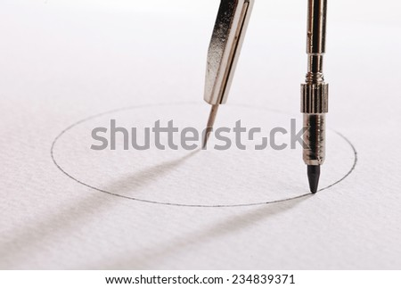 pair of compasses drawing circle on a paper - stock photo