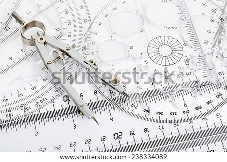 pair of compasses on transparent rulers and protractors - stock photo