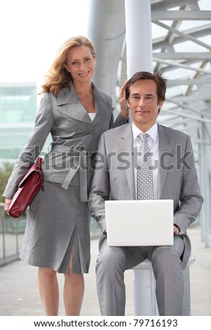 Pair of confident executives with laptop computer - stock photo