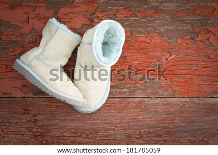 Pair of cozy warm winter sheepskin slippers lined with fluffy woolly fleece lying one upright and one on its side on rustic grunge wooden boards with red textured peeling paint and copyspace - stock photo
