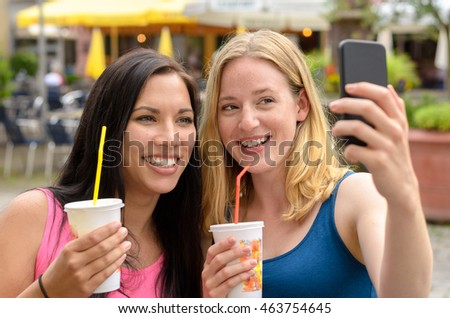 Pair of cute women with beverages in styrofoam cups taking self portraits at outdoor cafe