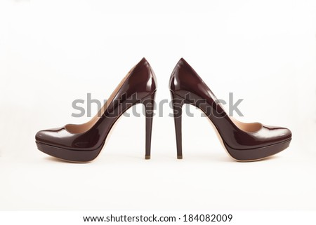 Pair of dark red designer stiletto high heels with a small platform and made of shiny patent leather.