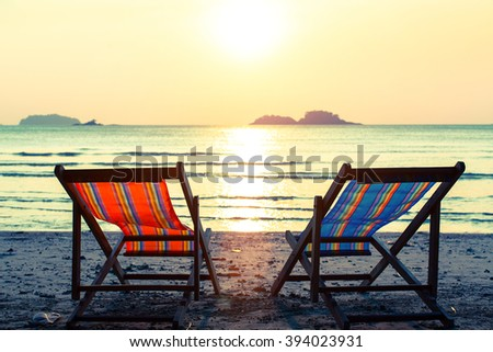 Pair of deckchairs on a Sunny beach. - stock photo