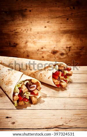 Pair of delicious chicken and veggie burritos laid neatly next to each other over wooden table with copy space in background - stock photo
