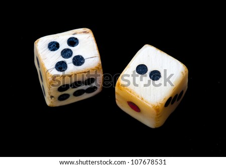 Pair of dice made of bone or ivory. Vintage or antique. Closeup isolated against black background. - stock photo