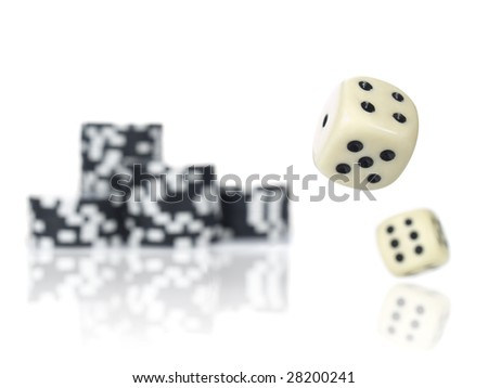 Pair of dice rolling in front of stacked black poker chips. - stock photo