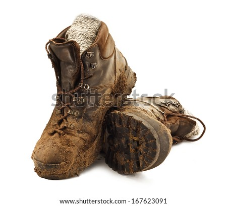 Pair of dirty brown walking boots covered in mud isolated on a white background - stock photo