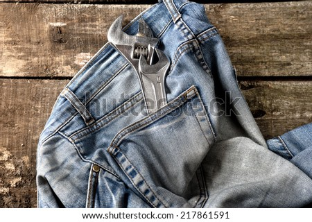 Pair of dirty jeans on floor with tools in the pocket - stock photo