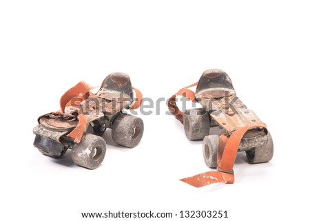 Pair of dirty rusty aged roller skates isolated over white - stock photo