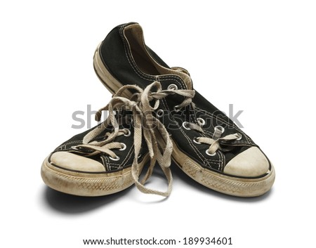 Pair of Dirty Worn Shoes Stacked on One Another Isolated on White Background. - stock photo