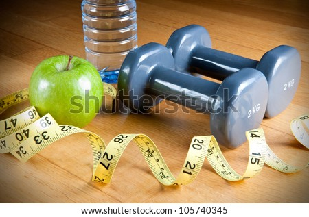 Pair of dumbbells, green apple, measuring tape and bottle of water. Exercise and healthy diet concept. - stock photo