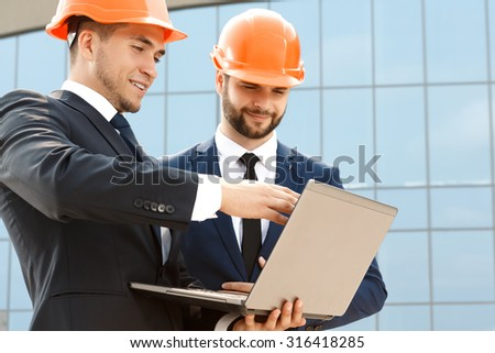 Pair of engineers examining their plans on laptop - stock photo
