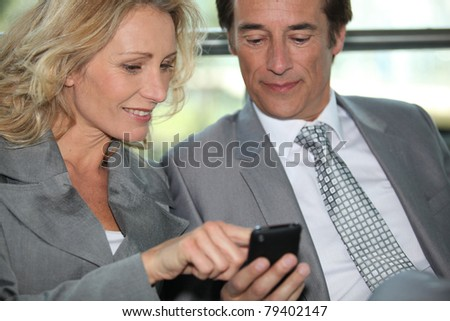 Pair of executives looking at something on a cellphone - stock photo