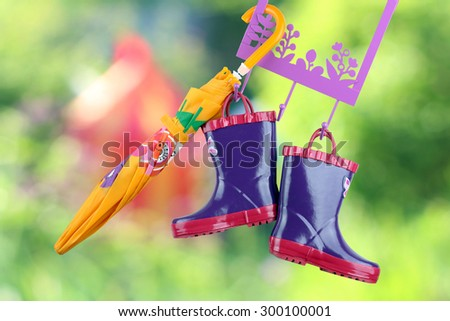 Pair of fashion rubber child boots  hanging with yellow umbrella - stock photo