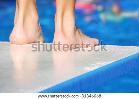 Pair of feet at edge of diving board, waiting for pool to clear before jumping - stock photo