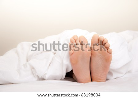 Pair of Feet in Bed on White Sheets - stock photo