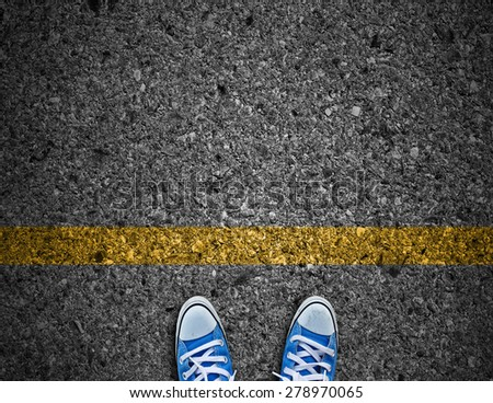 pair of feet on road with yellow line