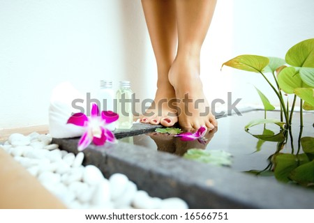 Pair of feminine feet by a sunken foot bath with foot lotion and soap on side - stock photo