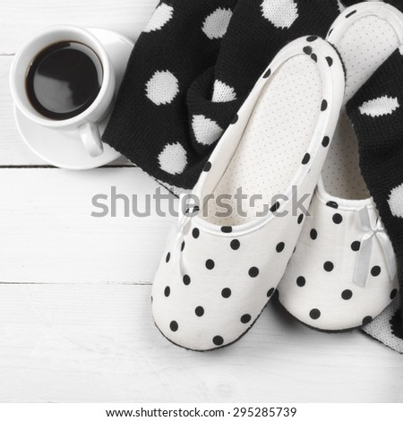 Pair of feminine slippers with white and black polka dot decor, woolen knitwear and cup of coffee on white wood. - stock photo