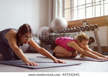 Pair of fit women stretching on mats in gym with weights and stability balls under window in background - stock photo