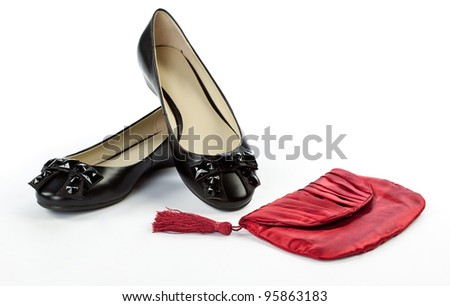 Pair of flat shoes and red handbag on white background; woman's accessories