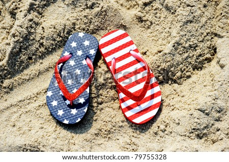 Pair of flip-flop on sand of Jersey shore with USA flag pattern on it - stock photo