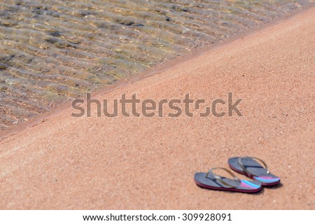 Pair of Flip Flop Thongs Resting Along Shoreline of Sandy Beach with Clear Water - stock photo
