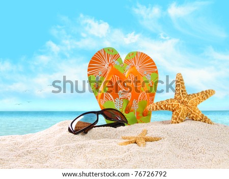 Pair of flip- flops in the sand with starfish - stock photo