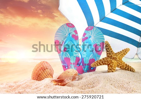 Pair of flip-flops in the sand with starfish at sunset - stock photo