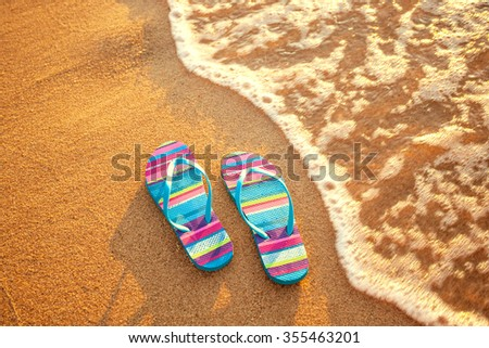 pair of flip-flops on a sandy beach at sunset, holiday and vacation concept - stock photo