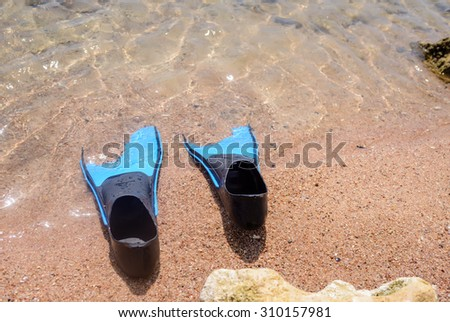 Pair of flippers on a beach lying half embedded at the edge of the sea with the water lapping around them, conceptual of a tropical summer vacation - stock photo