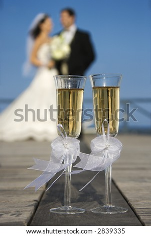 Pair of flute glasses of champagne with Caucasian bride and groom blurred in background. - stock photo