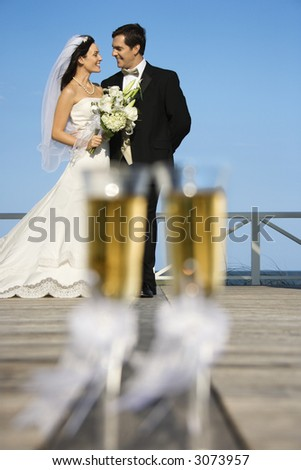 Pair of flute glasses of champagne with Caucasian bride and groom in background.