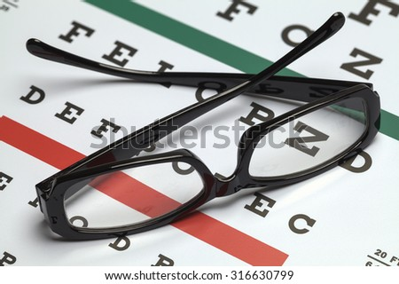 Pair of Folded Glasses on Eye Exam Chart. - stock photo