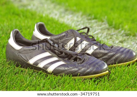 Pair of football boots on the grass - stock photo
