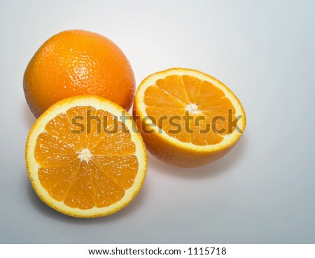 pair of fresh oranges, with one sliced in half exposing the sweet meaty interior - stock photo