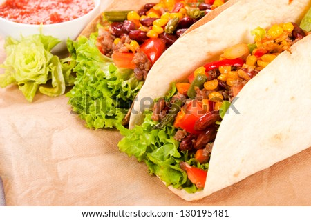 Pair of fresh tacos on the table. Selective focus on the front taco sandwich - stock photo