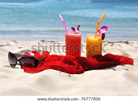 Pair of fruit shakes, red shawl and sunglasses on the tropical beach - stock photo