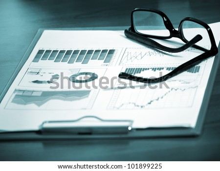 Pair of glasses on a financial chart - stock photo