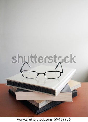 Pair of glasses on a stack of books - stock photo
