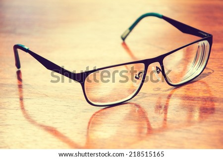 Pair of glasses on the wooden table (Vintage tone) - stock photo