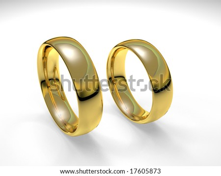 Pair of gold wedding rings in white background.