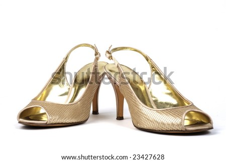 Pair of gold women's high-heel shoes against white background - stock photo