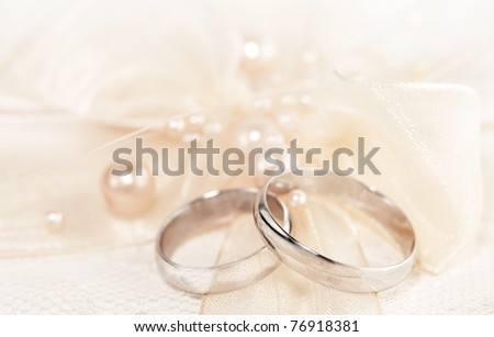 Pair of golden wedding rings over invitation card decorated with silk bow & pearls