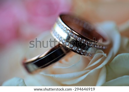 Pair of golden wedding rings with diamonds on bouquet of fresh flowers of pink and white roses closeup, horizontal picture - stock photo