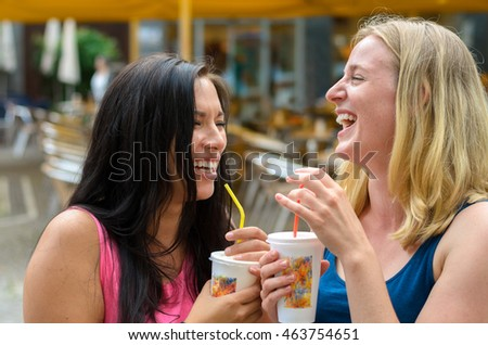 Pair of gorgeous happy women in sleeveless shirts with drinks while laughing at outdoor cafe