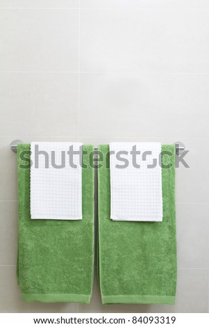 Beau Pair Of Green And White Towels On A Rail In A Tiled Bathroom Setting